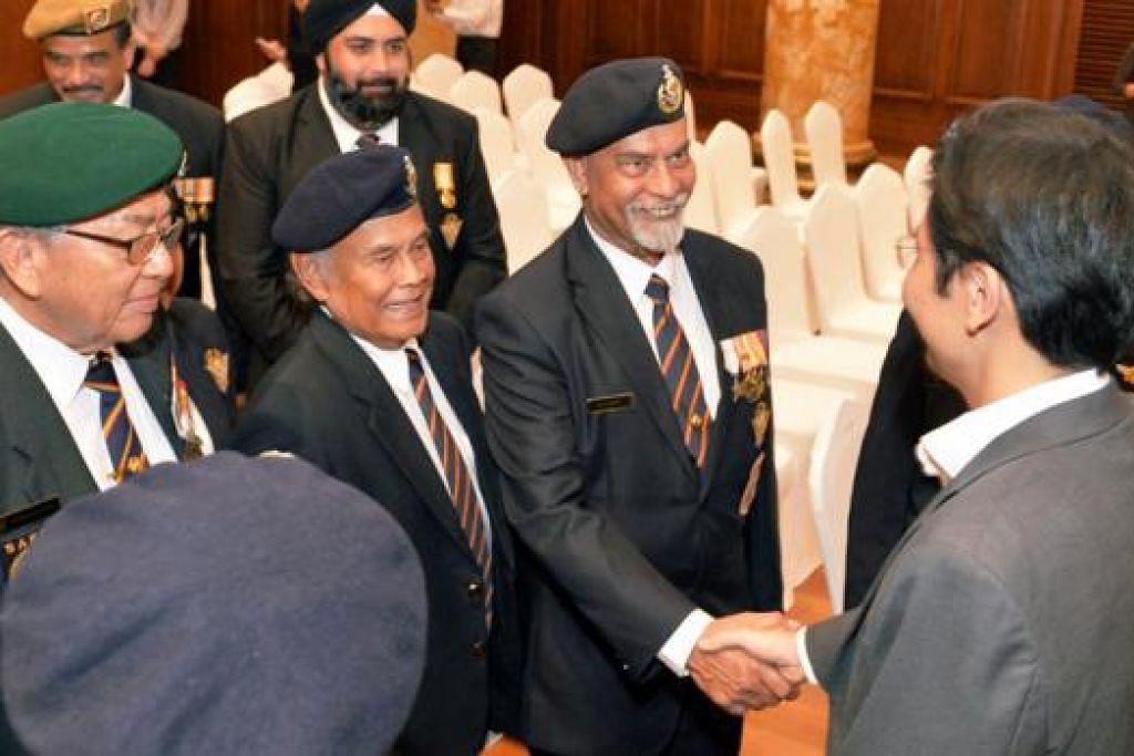 PERINGATI JASA PERINTIS: Encik Lawrence Wong (kanan) berjabat tangan dengan Encik Mohd Saleh, salah seorang perajurit perang semasa pendudukan tentera Jepun di Singapura. - Foto KHALID BABA