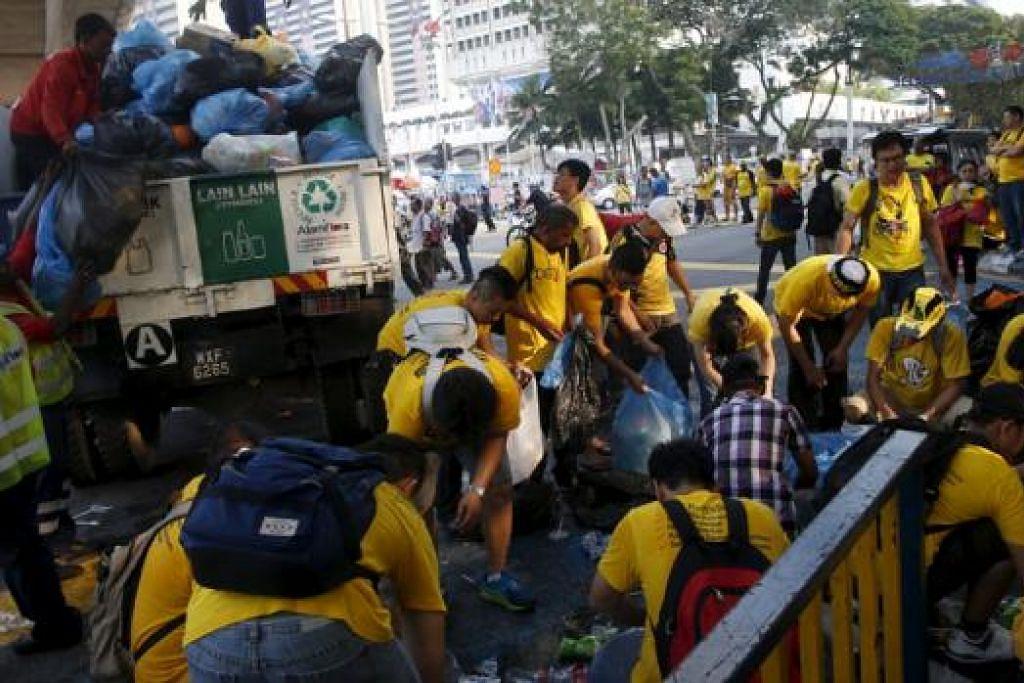 BERSIHKAN JALAN: Peseta Bersih 4 bekerjasama membersihkan sampah sarap di jalan raya dekat kawasan luar Dataran Merdeka demi memelihara kebersihan di tempat mereka melakukan tunjuk perasaan. - REUTERS