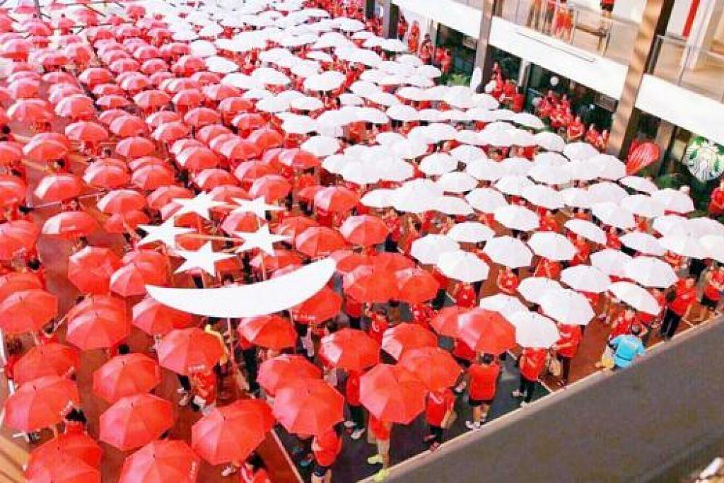 KREATIVITI MENYERLAH: Peserta acara berjalan kaki beramai-ramai 'One Community Walk' ini menggunakan payung merah dan putih bagi membentuk formasi persis bendera Singapura. - Foto PERSATUAN RAKYAT
