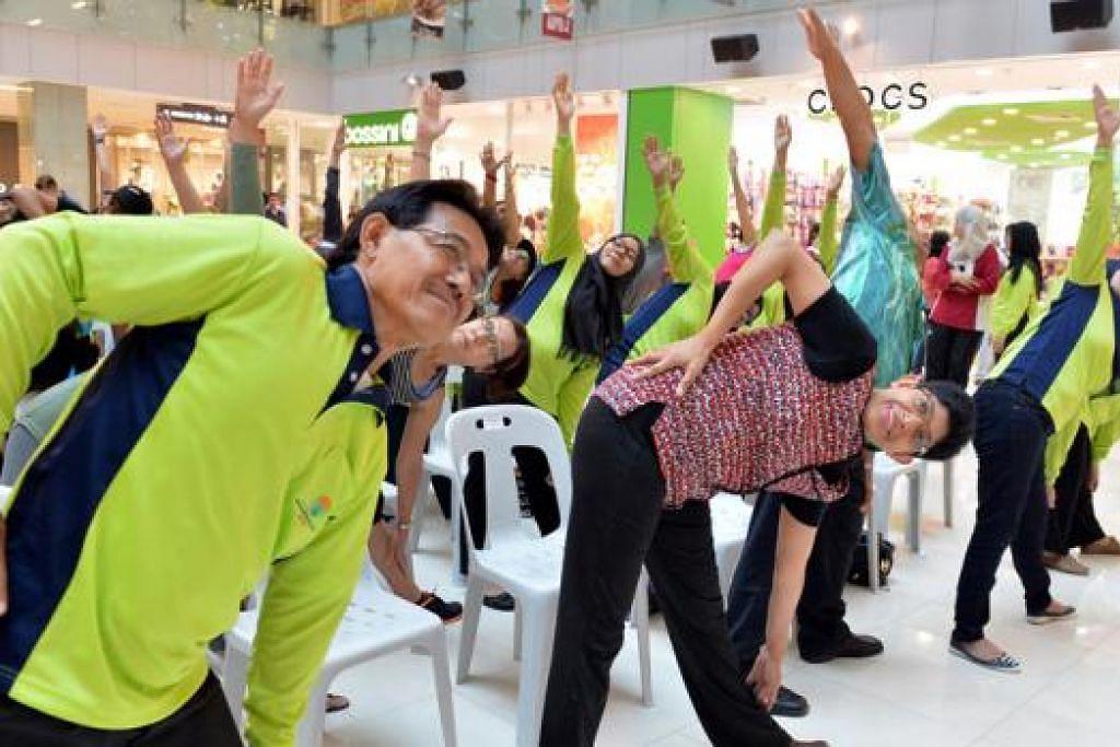 PROGRAM GAYA HIDUP SIHAT: Dr Fatimah (tengah) menyertai sesi yoga yang diadakan sebagai sebahagian daripada pelancaran Program Gaya Hidup Sihat di pusat beli-belah One KM Mall kelmarin. - Foto M.O. SALLEH