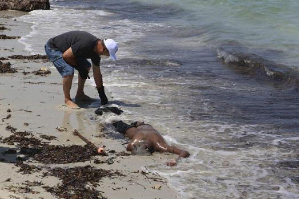TEMUI MAYAT: Seorang pekerja Palang Merah Libya memeriksa mayat pendatang tanpa izin yang ditemui pengawal pantai negara itu selepas sebuah bot karam dekat perairan Zuwara di Libya Khamis lalu. - Foto REUTERS