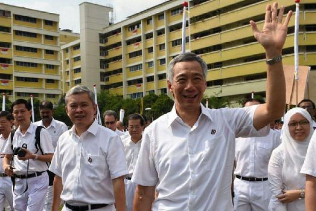 LAMBAIAN KEPADA PENYOKONG: Perdana Menteri Lee Hsien Loong bersama pasukannya daripada Parti Tindakan Rakyat (PAP) melambai kepada penyokong sambil melangkah ke pusat pencalonan di Raffles Institution untuk memfailkan dokumen. - Foto AFP