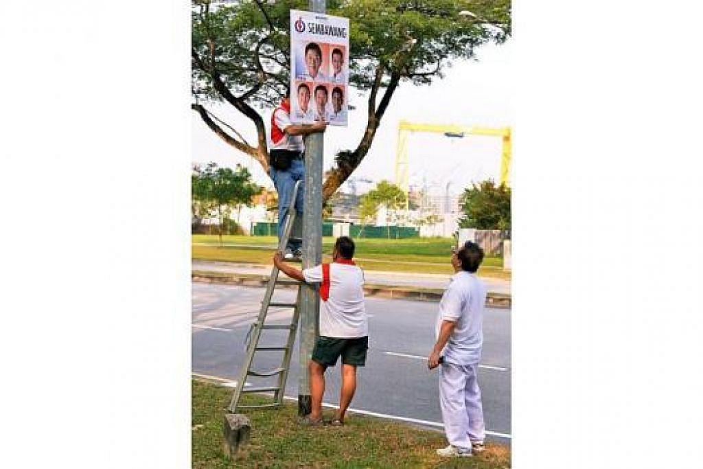 KEMPEN SUDAH BERMULA: Para pekerja menggantung papan kempen bagi calon PAP GRC Sembawang. – Foto KHALID BABA