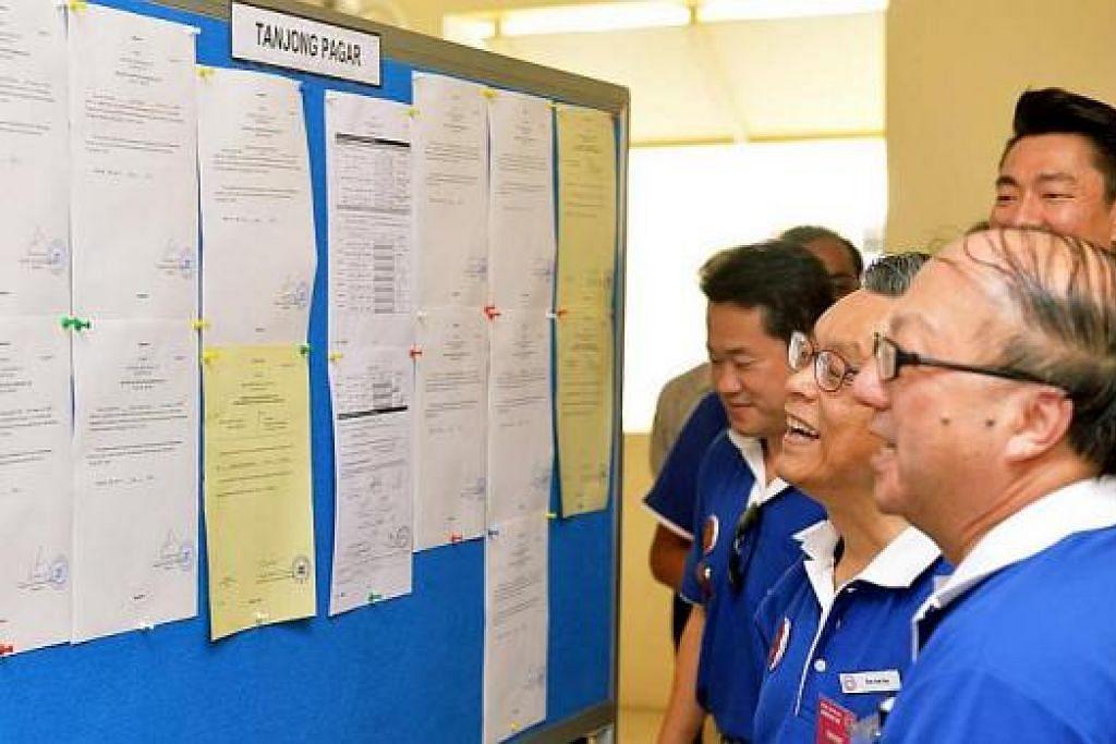 TERSENYUM LEBAR: Anggota parti pembangkang SingFirst – (dari kanan) Encik Ang Yong Guan, Encik Tan Jee Say, Encik Fahmi Rais dan Encik Melvyn Chiu(belakang) – kelihatan sempat berjenaka semasa menyemak borang permohonan mereka di papan notis selepas memfailkan pencalonan masing-masing di Sekolah Rendah Bendemeer. – Foto KHALID BABA