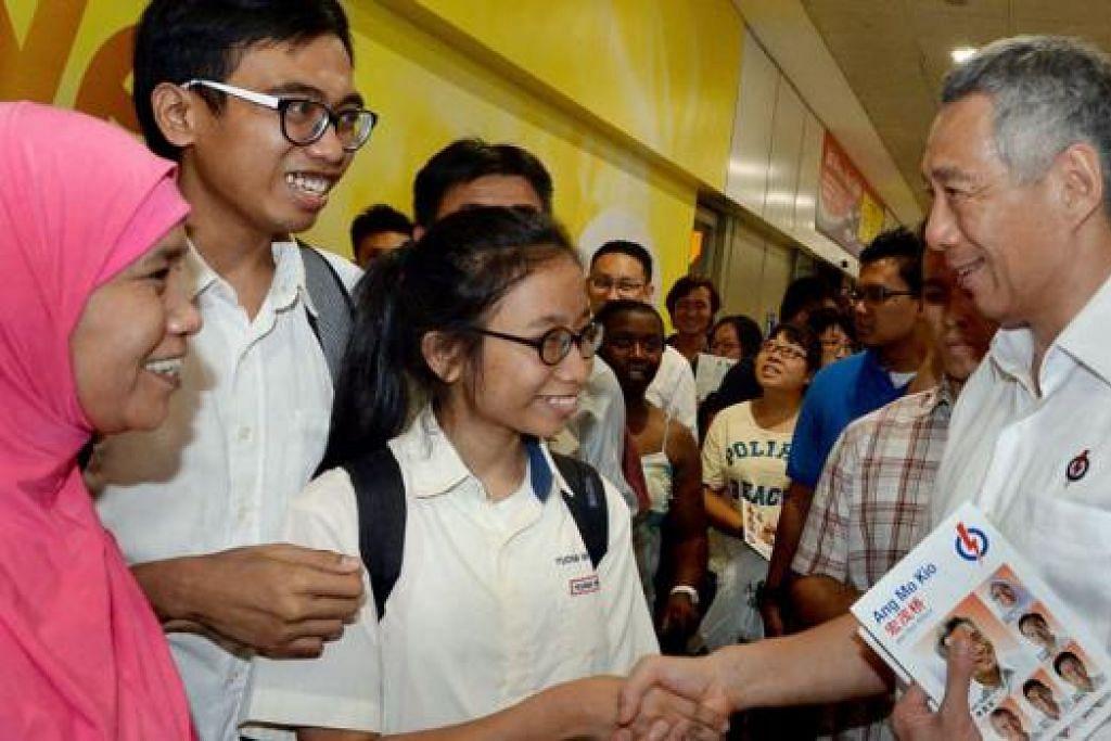 BERAMAH BERSAMA PERDANA MENTERI: Encik Lee Hsien Loong melawat Ang Mo Kio Central untuk bertemu penduduk di situ selepas sidang media yang diadakan malam semalam. - Foto TAUFIK A. KADER