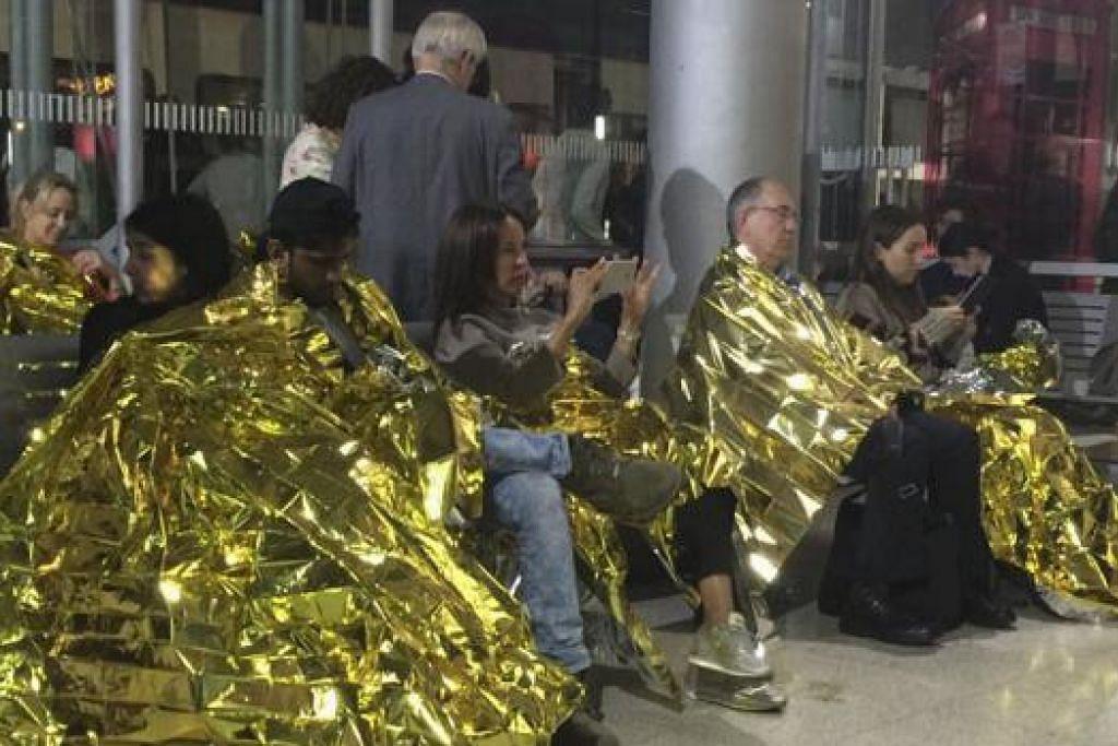 KESEJUKAN: Para penumpang diberikan selimut haba selepas kereta api Eurostar yang dinaiki terkandas di Stesen Calais. - Foto REUTERS