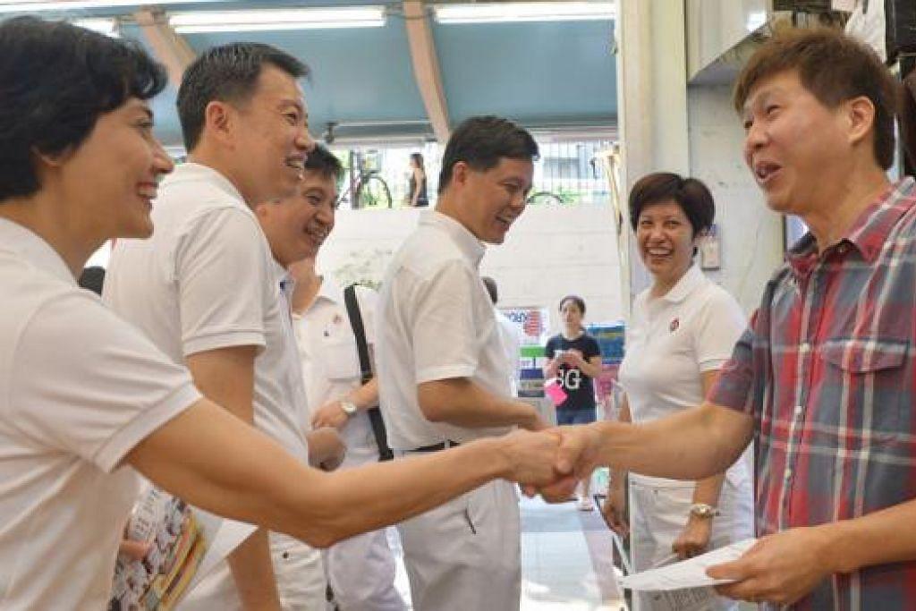 TEMUI PENDUDUK: Pasukan PAP bagi GRC Tanjong Pagar, (dari kiri) Cik Joan Pereira, Encik Melvin Yong, Encik Chia Shi-lu, Encik Chan Chun Sing, dan Cik Indranee Rajah, bertemu seorang penduduk di MRT Tiong Bahru, semalam.