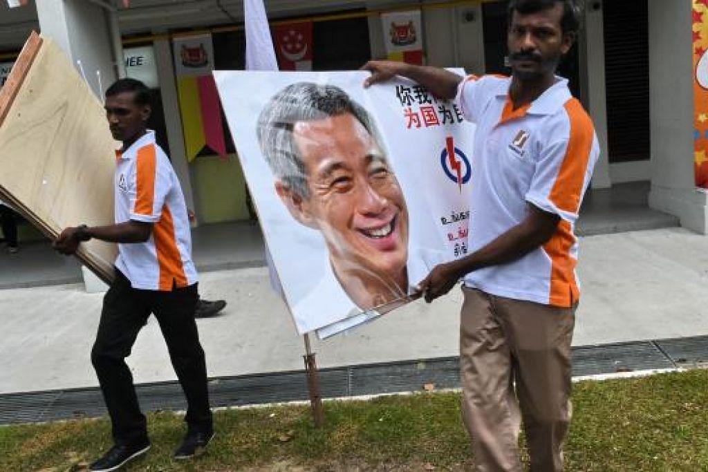 Pekerja membawa poster PAP yang memapar wajah pemimpinnya, Perdana Menteri Lee Hsien Loong, untuk dipasang di seluruh negara. Memasang poster pemimpin parti politik di kawasan undi yang tidak ditandinginya turut diamalkan pada pilihan raya umum sebelum ini. Gambar AFP