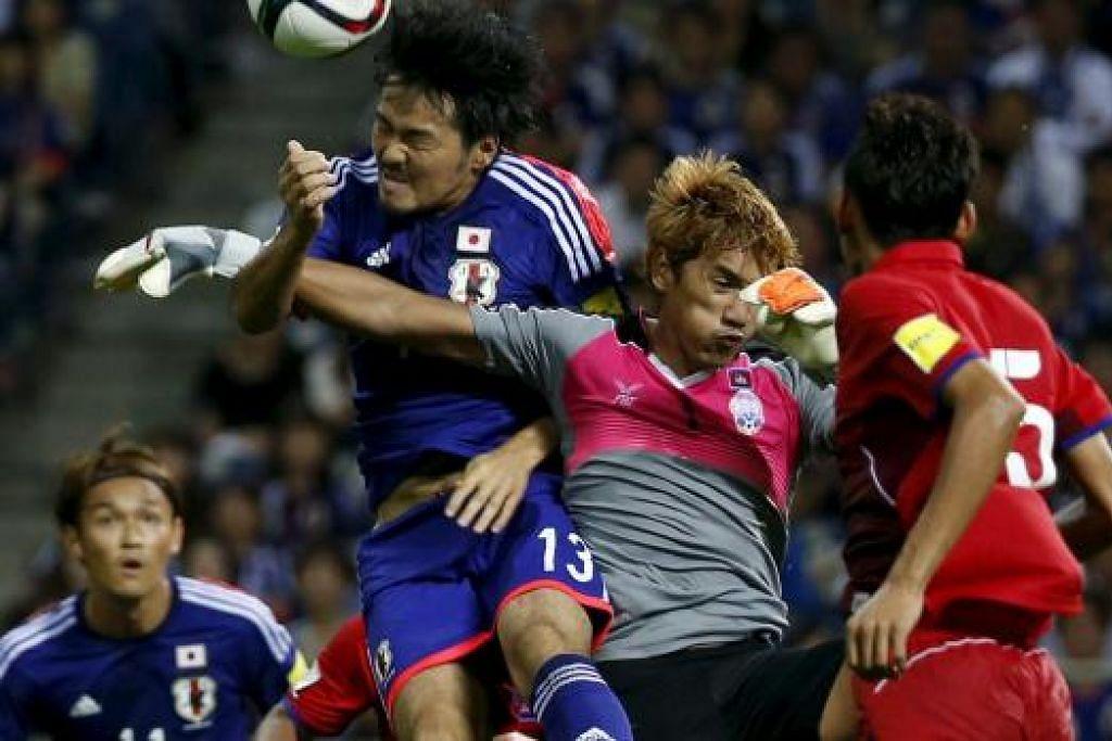 REBUT BOLA: Pemain Jepun, Shinzoh Kohrogi (jersi biru) melompat tinggi bagi bersaing bola dengan penjaga gawang Kemboja, Sou Yaty, dalam pertarungan kelayakan Piala Dunia 2018 yang dimenangi Jepun 3-0.
