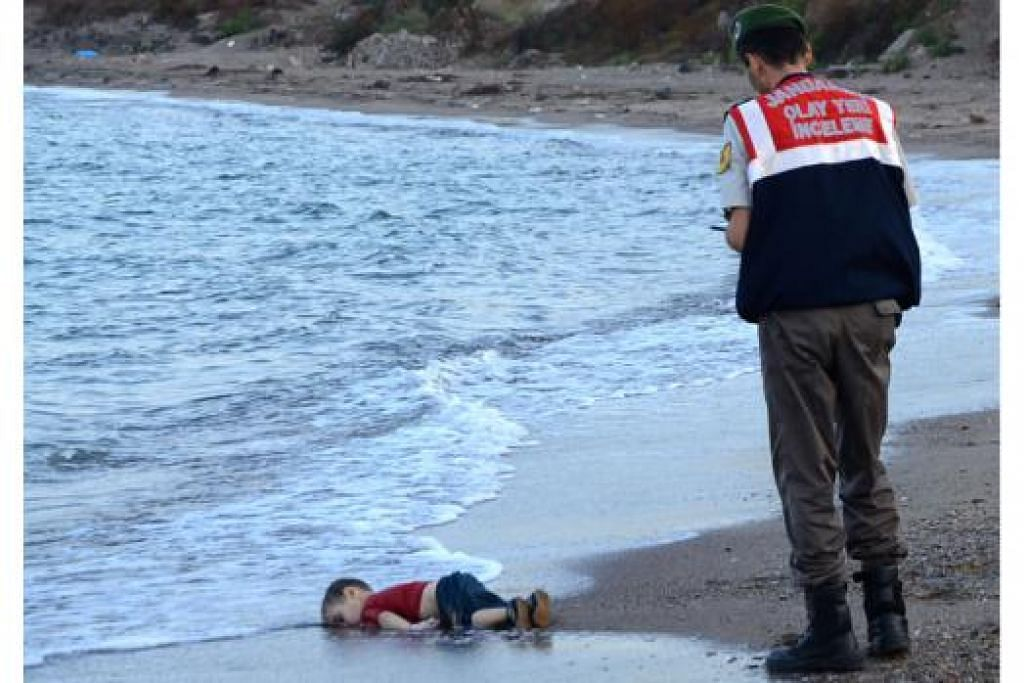 MEMILUKAN: Seorang pegawai polis Turkey berdiri di samping mayat anak pelarian yang terdampar di pantai Bodrum, selatan Turkey, Rabu lalu selepas bot yang membawa pelarian Syria karam ketika mendekati kepulauan Kos di Greece. - Foto AFP