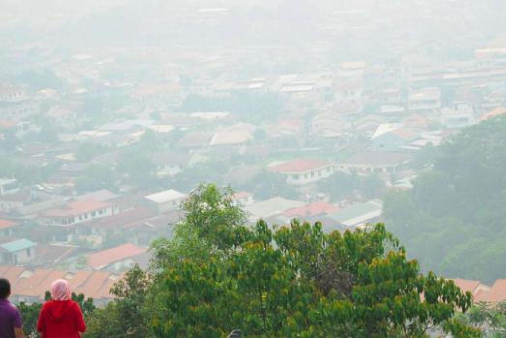 BERKABUS: Pemandangan berkabus dari bukit di Hulu Langat di Ampang, kelmarin. – Foto AFP