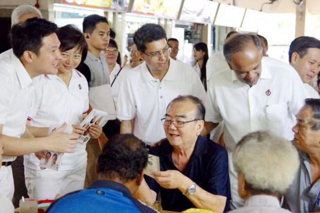 PRIHATIN AKAN PENDUDUK: Encik Shanmugam (berdiri, dua dari kanan) bersama pasukannya yang terdiri daripada (dari kiri, berdiri) Encik Kwek, Dr Lee, Dr Muhammad Faishal dan Encik Ng bertemu penduduk untuk mendapatkan maklum balas mereka. - Foto IMMANUEL ROSZIN