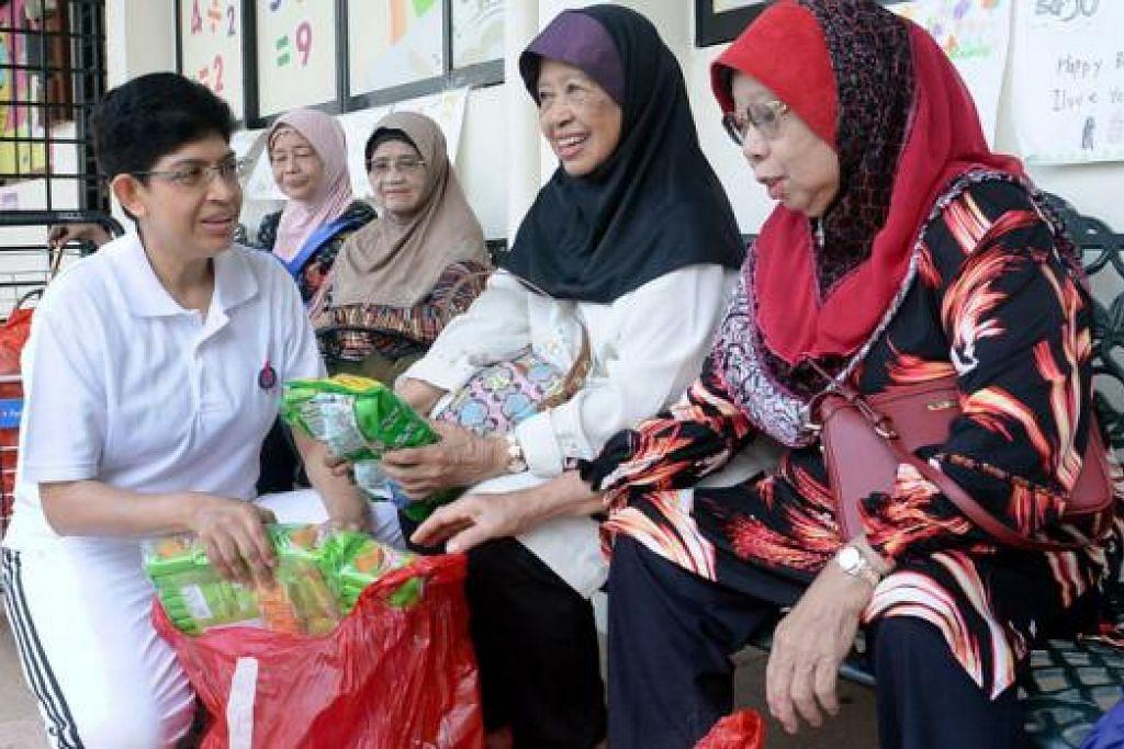 SENTIASA BERSEDIA HULUR KHIDMAT: Dr Fatimah (kiri) mengagihkan makanan kering kepada golongan memerlukan itu berlangsung semalam. - Foto TAUFIK A. KADER
