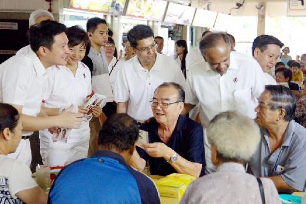 Encik Shanmugam (berdirin kanan) bersama pasukannya bertemu penduduk GRC Nee Soon. Gambar THE STRAITS TIMES