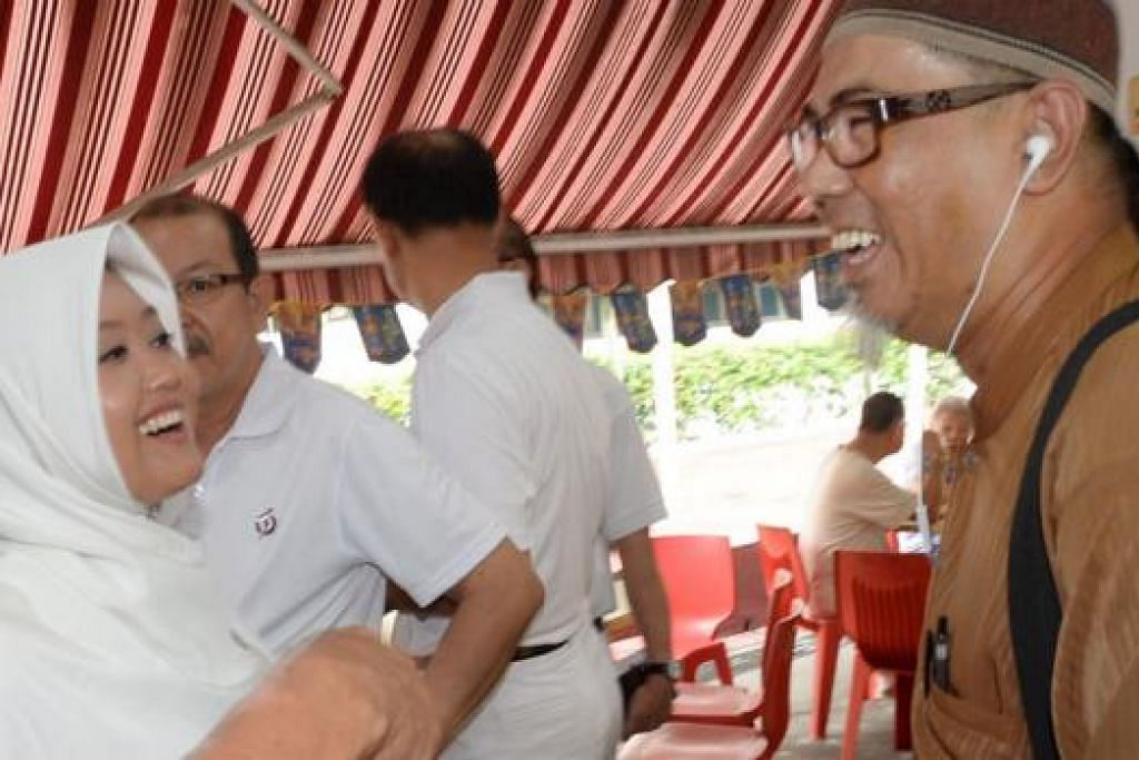 RANCAK BERKEMPEN: Cik Rahayu memperkenalkan dirinya kepada penduduk dan beramah mesra dengan mereka, termasuk Encik Amin (kanan), di sebuah kedai kopi di Blok 267A Toh Guan Road, semalam. - Foto JOHARI RAHMAT
