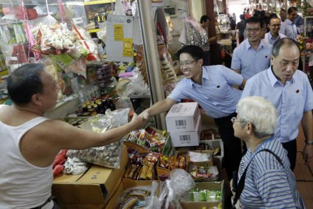 TURUN PADANG: Encik Giam (dua dari kiri) berjabat tangan dengan seorang pegerai semasa lawatannya ke pusat penjaja makanan dan pasar di Blok 58 New Upper Changi Road bersama calon WP lain di GRC East Coast dan Setiausaha Agung WP, Encik Low (kanan). - Foto THE STRAITS TIMES