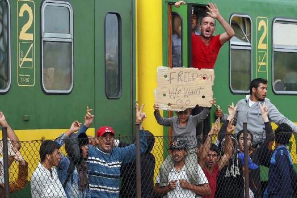 MEMBUAT BANTAHAN: Pendatang asing membuat bantahan di stesen rel di bandar Bicske, Hungary, selepas diarahkan berpindah ke khemah pelarian. - Foto REUTERS