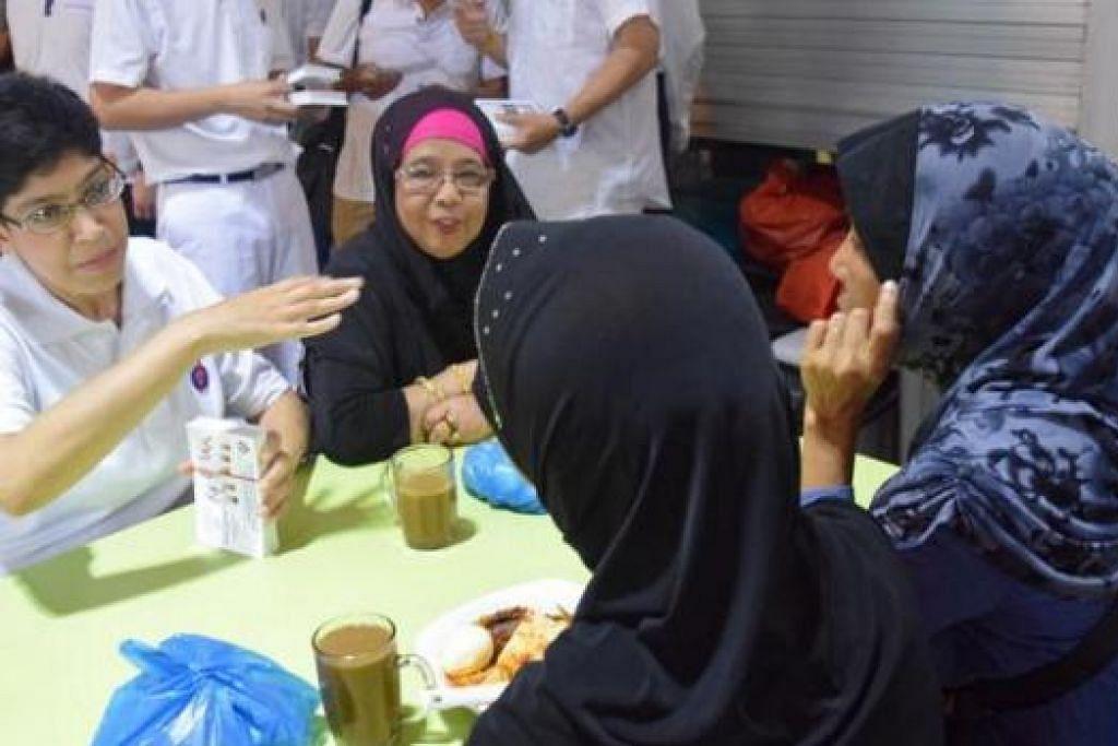 RESPONS POSITIF: Dr Fatimah (kiri) berinteraksi bersama penduduk yang sedang bersarapan pagi di pusat makanan Eunos Crescent. - Foto HAKIM YUSOF