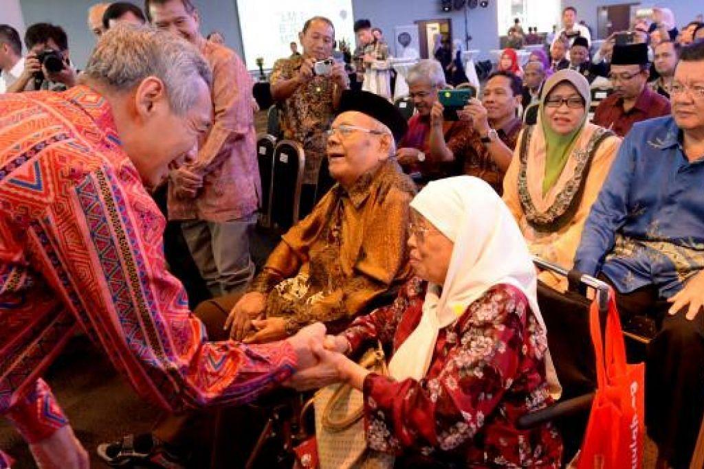 HARGAI JASA TERHADAP BAHASA: PM Lee bersalaman dengan Pendeta Dr Muhammad Ariff Ahmad serta isterinya yang menghadiri majlis pelancaran Bulan Bahasa 2015 di Taman di Persisiran