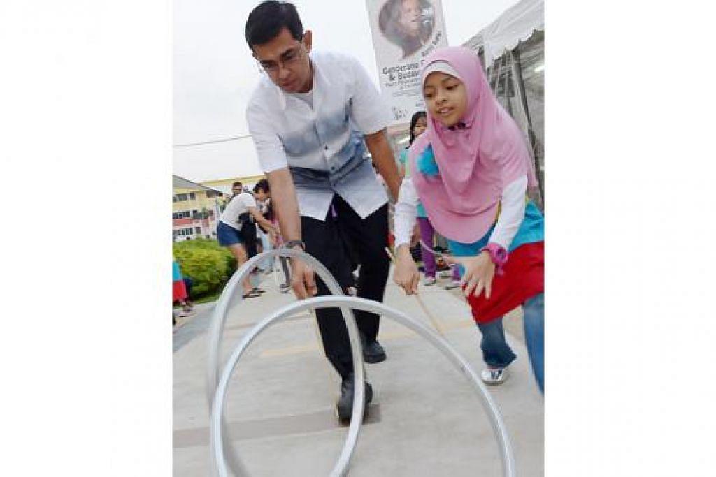 CUBA PERMAINAN LAMA: Encik Mohamad Fazlan Abdul Wahab bersama anaknya Aniis Nurinsyirah mencuba permainan tradisional 'lereng'. - Foto TUKIMAN WARJI