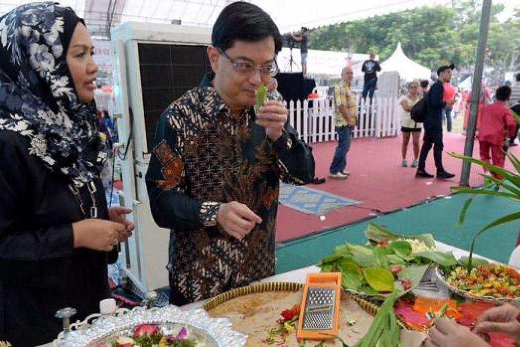 BELAJAR BUAT BUNGA RAMPAI: Encik Heng mengunjung ke pameran kegiatan sampingan yang diadakan di Tampines semalam yang termasuk demonstrasi bunga rampai. - Foto TUKIMAN WARJI