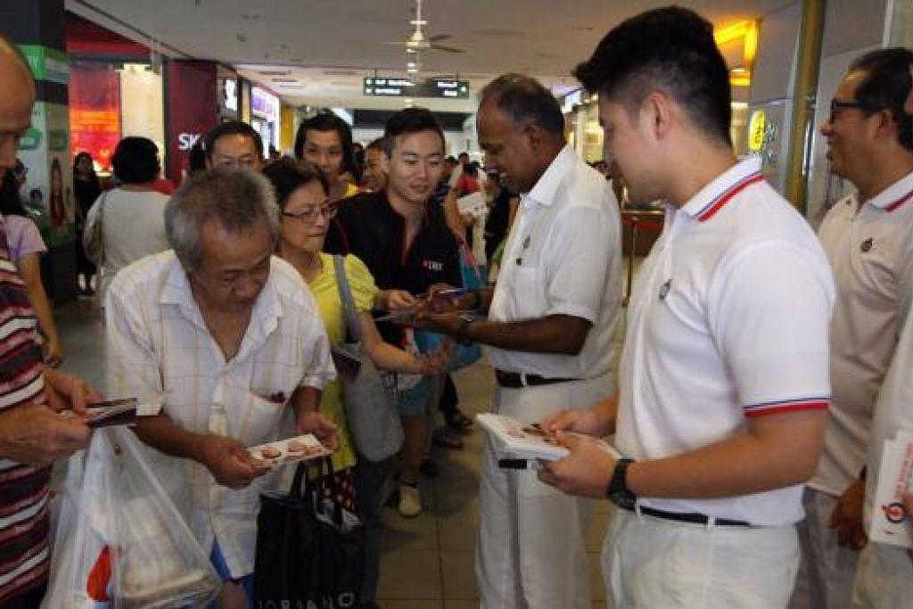 DEKATI PENDUDUK: Encik Shanmugam (tengah) sedang memberikan risalah PAP kepada penduduk di GRC Nee Soon semalam. - Foto IMMANUEL ROSZINI