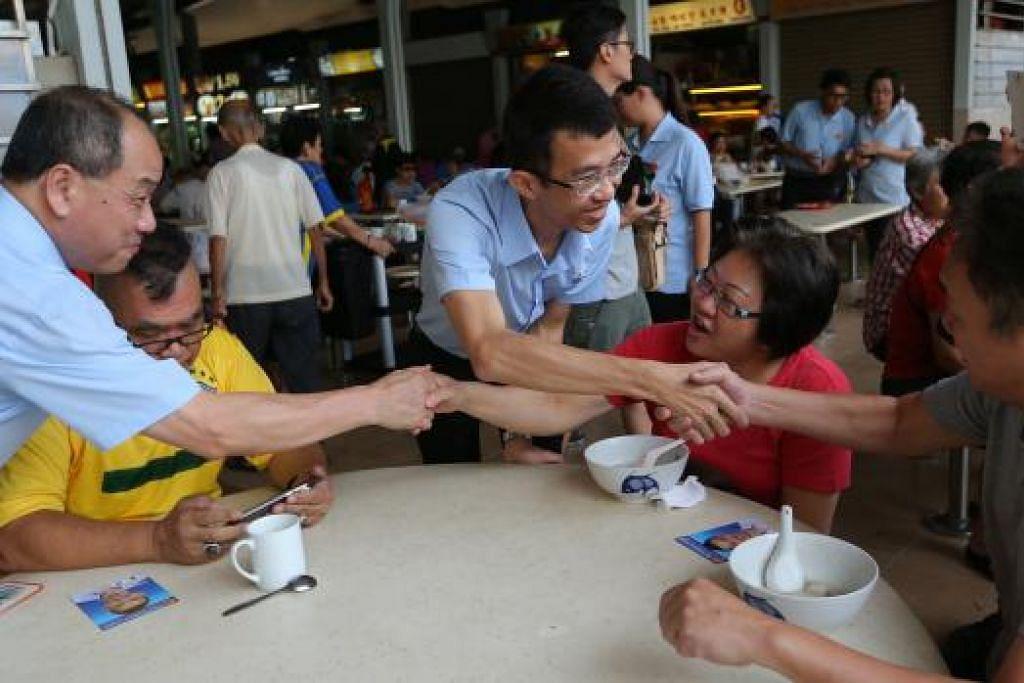 KENALKAN CALON: Encik Low (kiri) mengenalkan calon WP di MacPherson, Encik Bernard Chen (tiga dari kiri), kepada penduduk di kawasan undi itu semalam. - Foto THE STRAITS TIMES