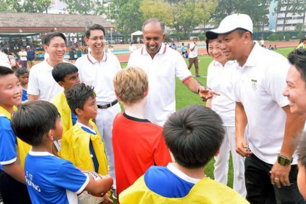 SERONOK BERINTERAKSI: Encik Shanmugam (tengah) dan anggota pasukan Parti Tindakan Rakyat (PAP) GRC Nee Soon lain bersama-sama dengan Fandi Ahmad (bertopi) berinteraksi dengan pelajar yang terlibat dalam Program Bola Sepak Sambil Belajar Nee Soon. - Foto KHALID BABA