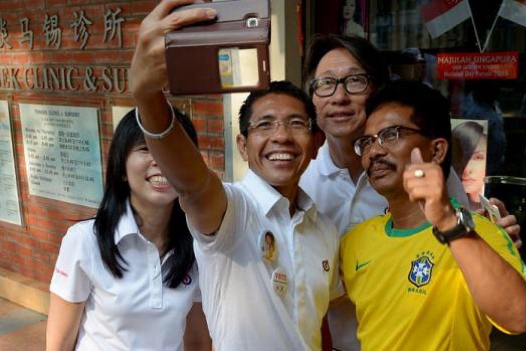 BERAMAH TAMAH DENGAN PENDUDUK: Calon GRC East Coast, (dari kiri) Cik Jessica Tan, Dr Mohamad Maliki Osman dan Encik Lim Swee Say, mengambil 'selfie' bersama seorang penduduk semasa sesi melawat penduduk di kawasan Bedok South Avenue 3 semalam. - Foto TUKIMAN WARJI