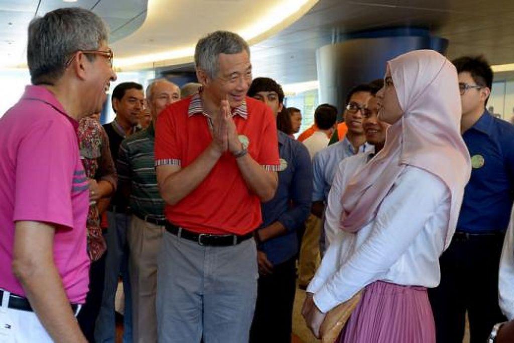 BERAMAH MESRA: Perdana Menteri, Encik Lee Hsien Loong (berbaju jingga), bersama Dr Yaacob Ibrahim (kiri) beramah mesra dengan hadirin Rahmatan Lilalamin (RLA) dalam pelancaran Bulan RLA semalam. - Foto TUKIMAN WARJI