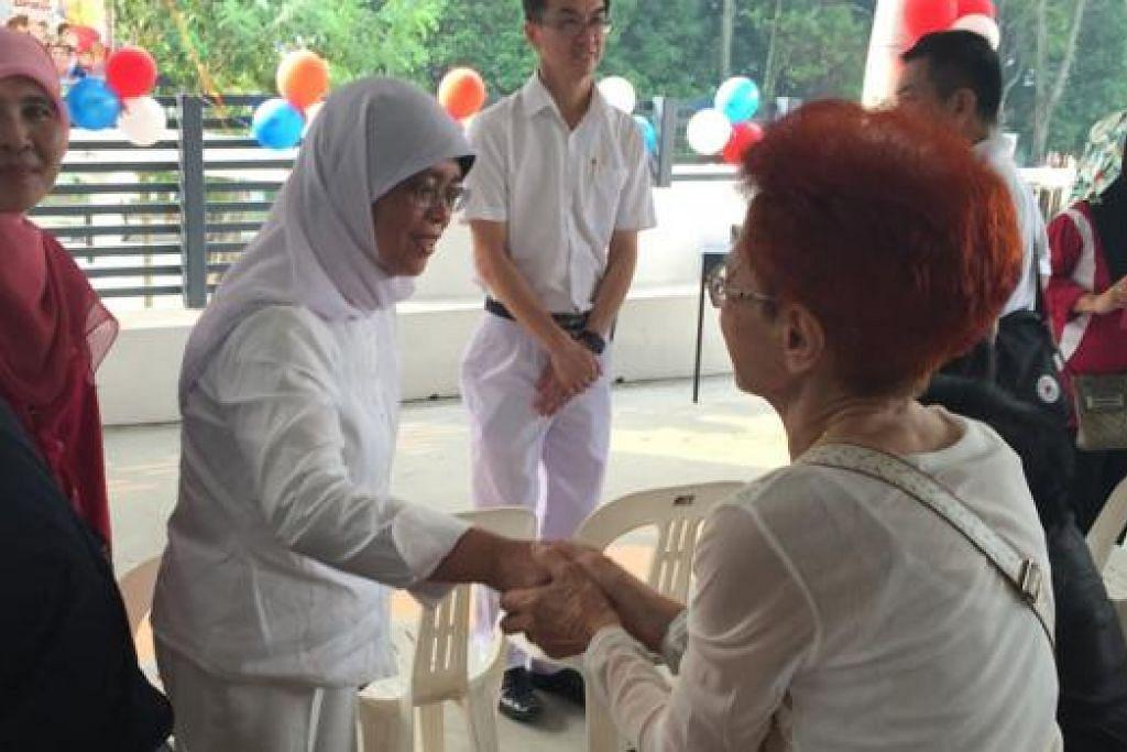 BINA KEPERCAYAAN DENGAN PENDUDUK: Cik Halimah Yacob (berbaju putih) mengunjungi pesta penduduk yang diadakan di Blok 180 di Marsiling semalam untuk berinteraksi bersama mereka. - Foto SITI AISYAH NORDIN