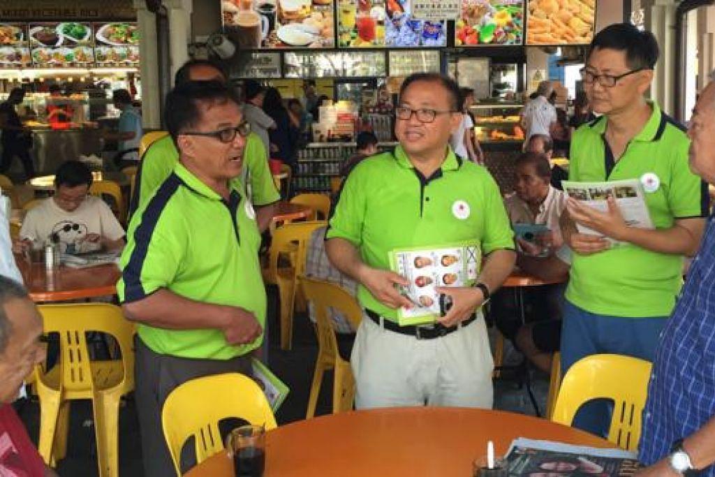 MENDEKATI PENDUDUK: Calon SDA (dua dari kiri) Encik Abu Mohamed, Encik Desmond Lim dan Encik Wong Way Weng mengunjungi beberapa kedai kopi di sekitar kawasan Pasir Ris Drive 6 untuk berinteraksi dengan penduduk. - Foto SITI AISYAH NORDIN