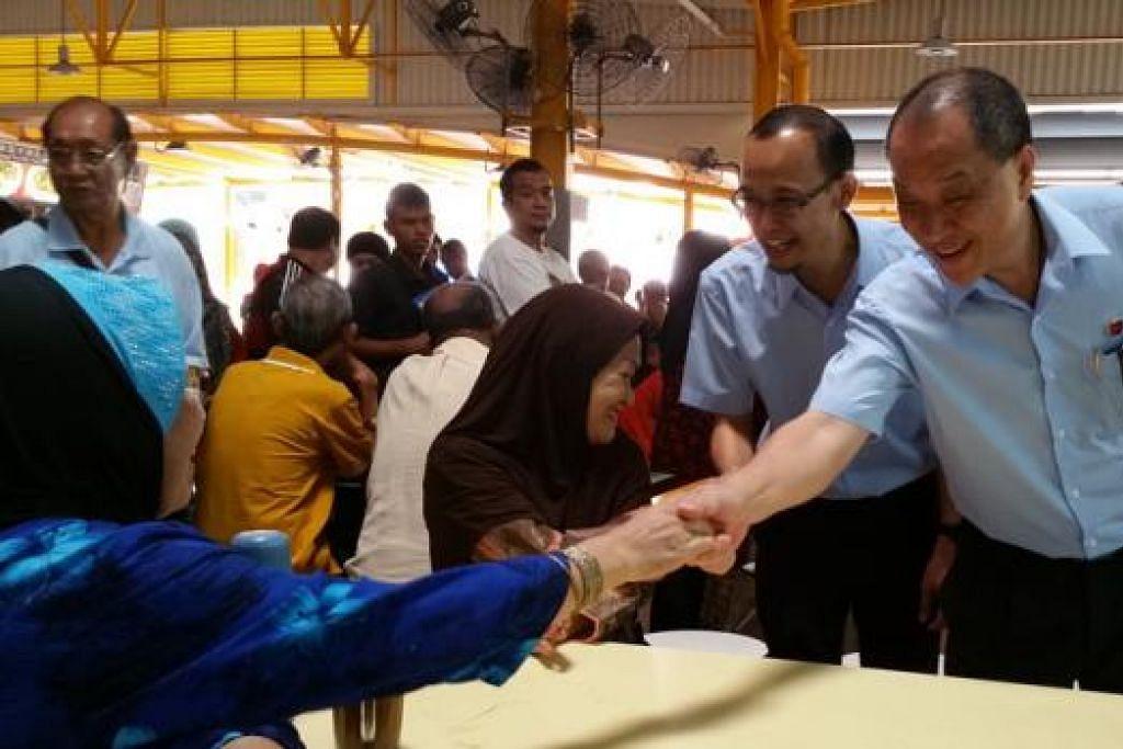TURUN PADANG: Encik Low Thia Khiang (kanan) dan calon GRC East Coast, Encik Encik Fairoz Shariff, beramah mesra dengan penduduk yang ditemui di Pusat Penjaja dan Pasar di Blok 16 Bedok South Road pagi semalam. - Foto AZAHAR MOHD
