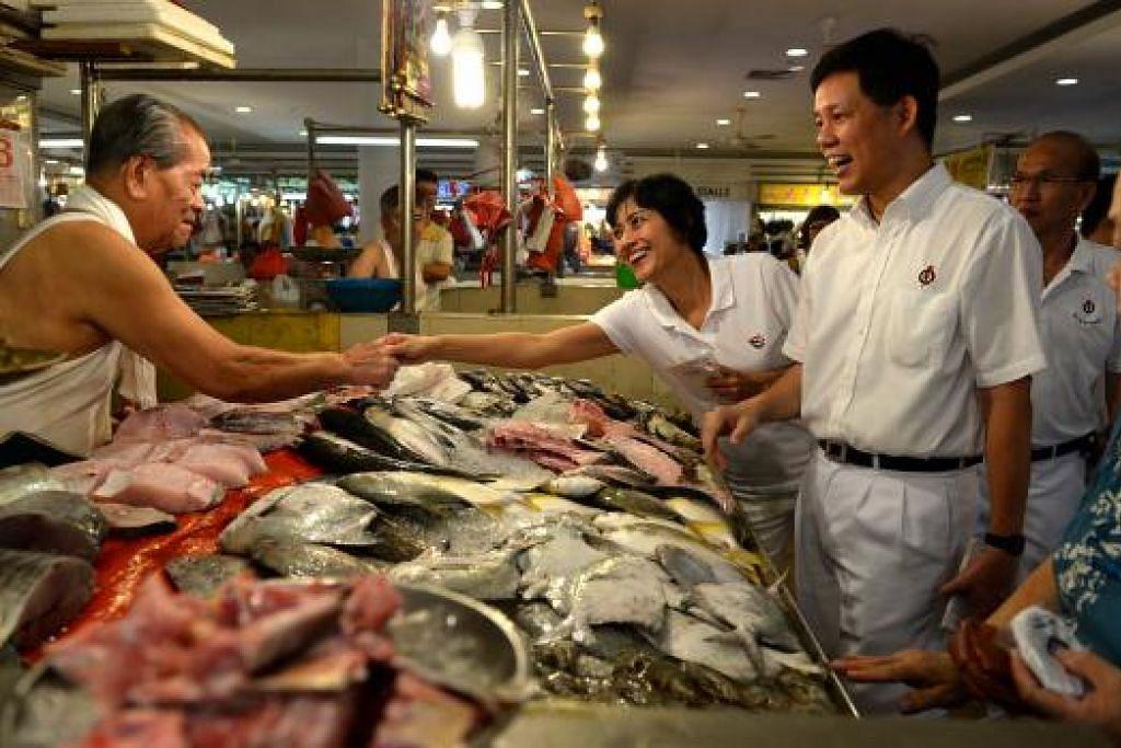 Encik Chan Chun Sing dan seorang rakan sepasukannya, Cik Joan Pereira, bertemu  penggerai di pasar Tiong Bahru di Blok 83. Gambar THE STRAITS TIMES