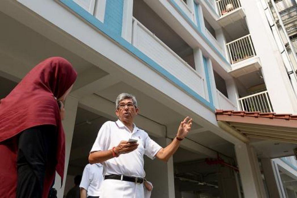 TANGANI ISU SETEMPAT: Dr Yaacob menunjukkan lif sebuah blok di Sims Drive yang mempunyai reka bentuk terbuka dan mendedahkan penduduk kepada panas terik dan hujan. Lif itu akan dipertingkat tahun depan. - Foto-foto TUKIMAN WARJI