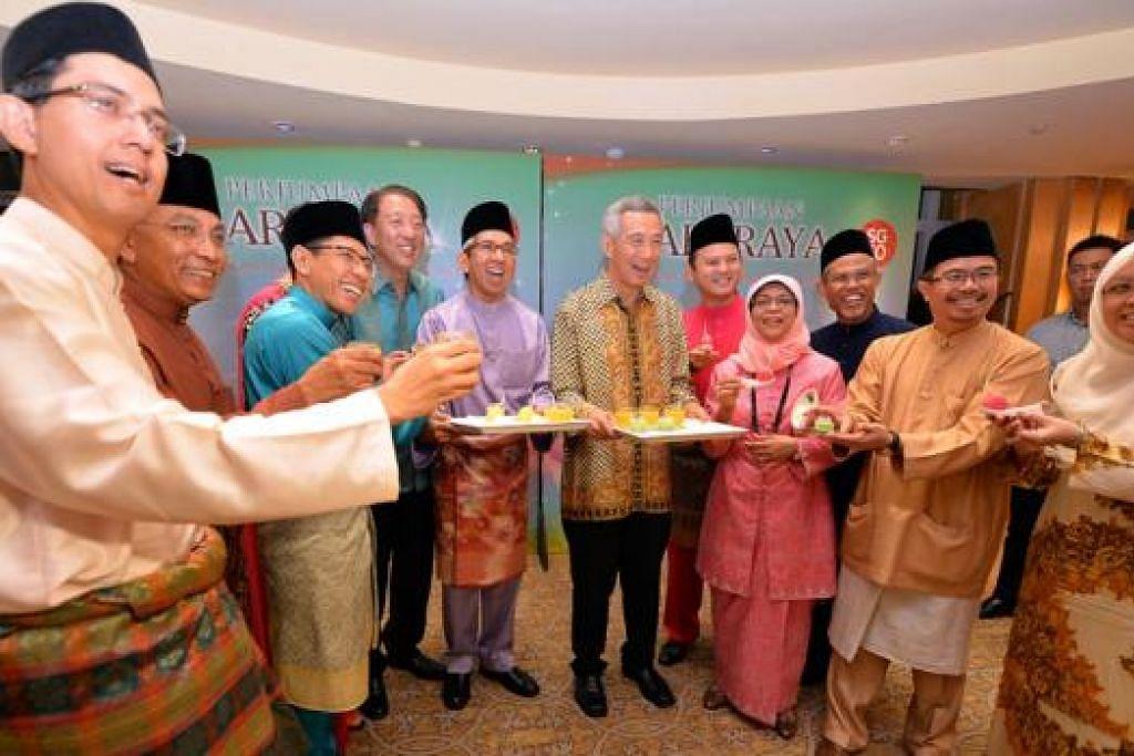 HUBUNGAN ERAT: Dr Yaacob (berbaju ungu) menekankan bahawa Anggota Parlimen Melayu PAP bekerjasama dengan pemerintah dan Perdana Menteri Lee Hsien Loong (di sebelah kirinya) bagi menyampaikan maklum balas serta sentimen masyarakat. - Foto fail