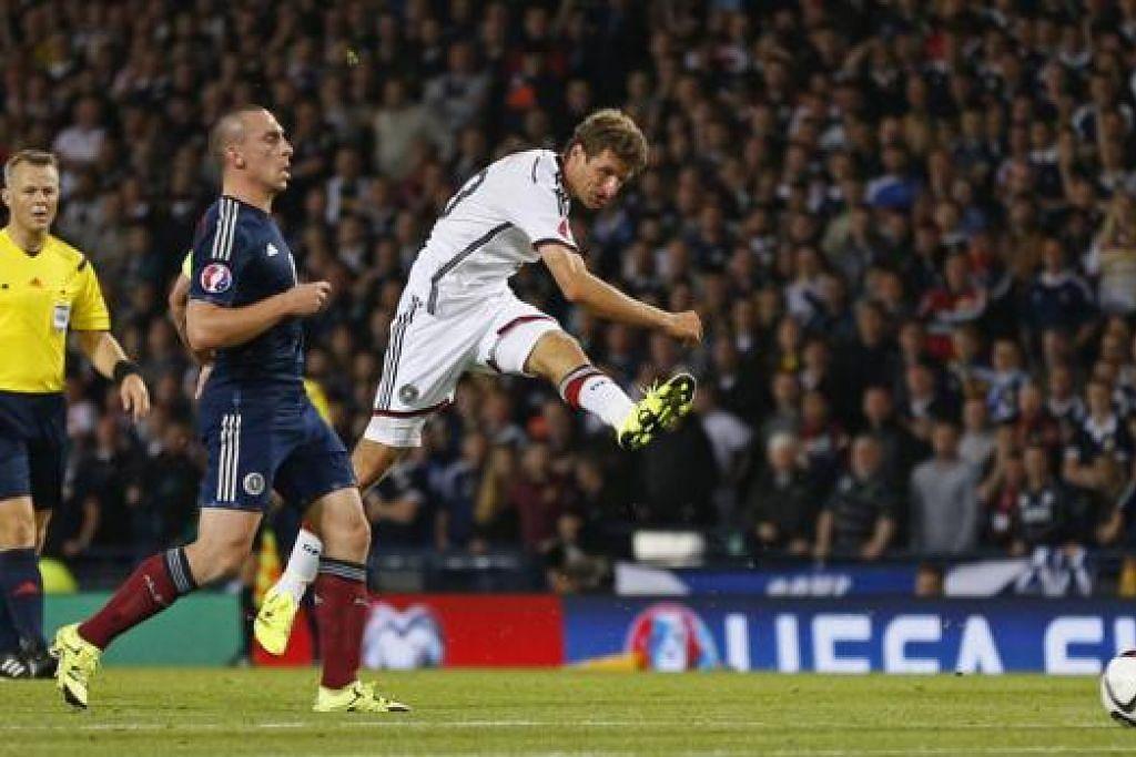 LEPASKAN REMBATAN: Penyerang Jerman, Thomas Mueller, merembat bola semasa menentang Scotland kelmarin. - Foto REUTERS