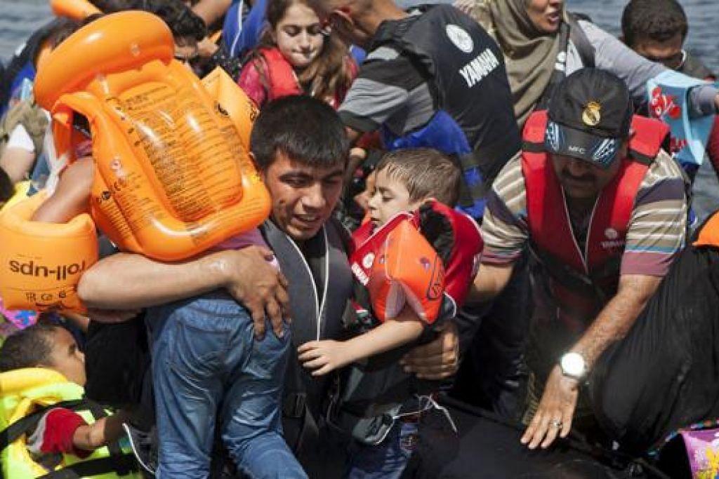 MERENTASI SEMPADAN: Seorang pelarian Syria membawa dua kanak-kanak selepas tiba dengan perahu kecil ke pulau Lesbos di Greece semalam. Greece bergelut untuk menampung beratus-ratus pendatang dan pelarian dari negara perang di Syria yang membuat lintasan pendek setiap hari dari Turkey ke pulau-pulau timur Greece, termasuk Kos, Lesbos, Samos dan Agathonisi. - Foto REUTERS