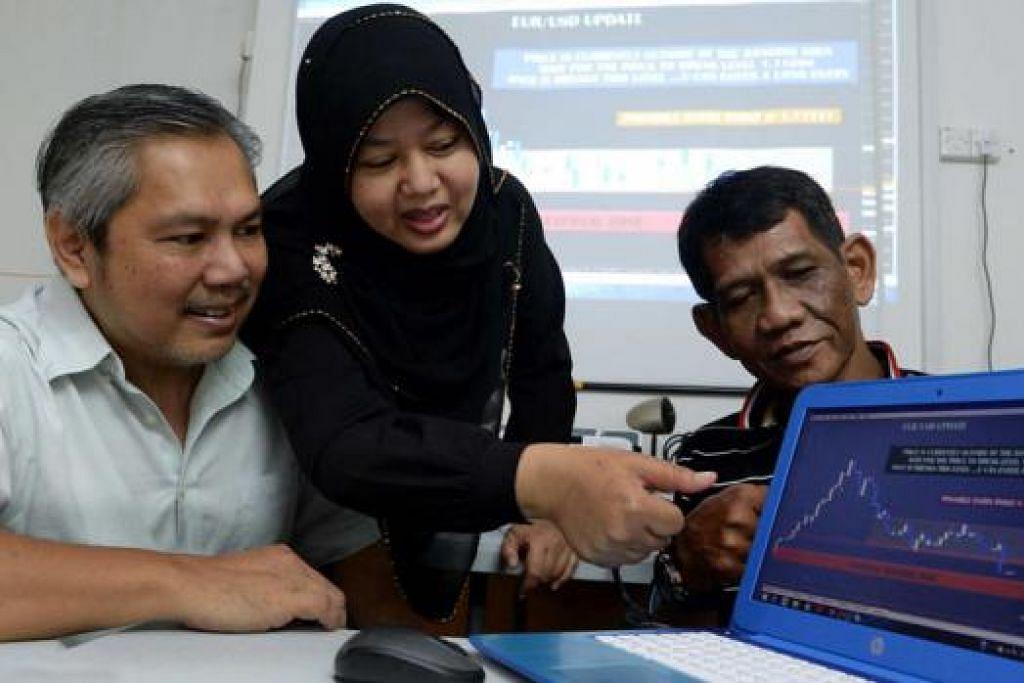 BELAJAR ILMU FOREX: (Dari kiri) Encik Kusni, Cik Supiah Safiie dan Encik Mustafa Haji Abdul Hamid merupakan perintis kumpulan THT Forex. - Foto TAUFIK A. KADER