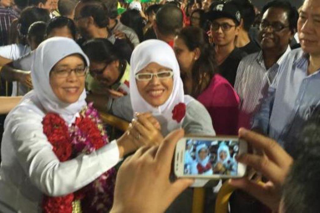 'SELFIE' BERSAMA PENYOKONG: Cik Halimah (kiri) meluangkan masa bersama hadirin yang mengunjungi rapat PAP di Stadium Woodlands, semalam. - Foto SITI AISYAH NORDIN