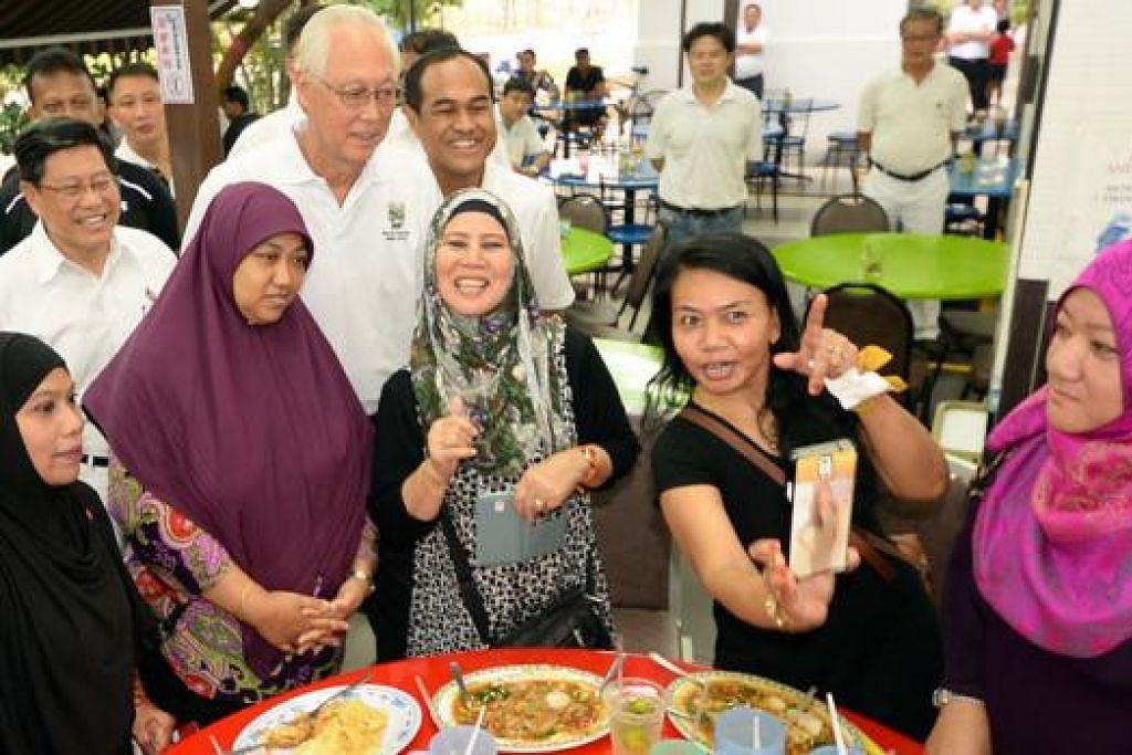 DEKATI PENDUDUK: (belakang dari kiri) Encik Yeo Guat Kwang, Encik Goh dan Encik Shamsul Kahar bergambar bersama penduduk. - Foto JOHARI RAHMAT