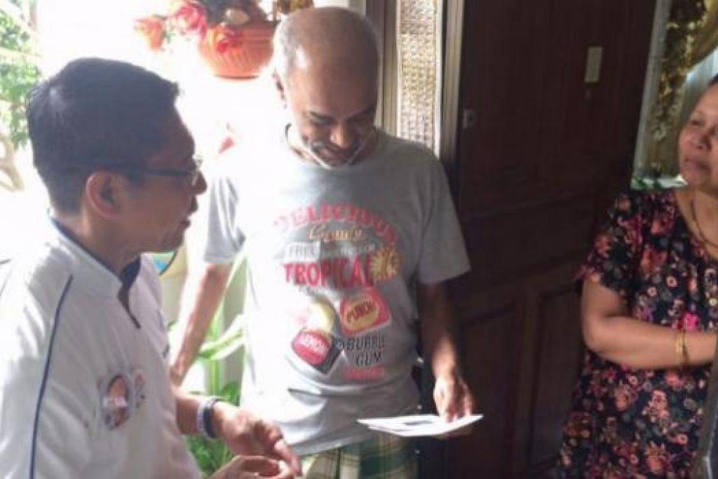 LAWATAN RUMAH KE RUMAH: Dr Maliki (kiri) bertemu dan mengedarkan risalah kepada Encik Azlan Abdul Sattar, 54 tahun, dan isterinya, Cik Latiffah Hassan, 53 tahun, salah seorang penduduk di Bedok South yang bakal membuang undi bagi memilih Anggota Parlimen GRC East Coast. - Foto HAIRIANTO DIMAN