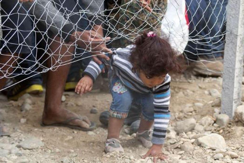 CUBA LOLOS DIRI: Seorang kanak-kanak perempuan ini merupakan antara pelarian yang cuba melintasi sempadan antara Greece dengan Macedonia dekat bandar Gevgelija. - Foto AFP