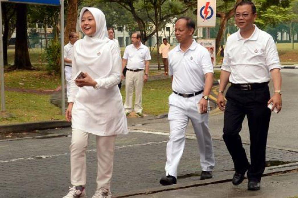 LIGAT TEMUI PENDUDUK: Meskipun pasukan PAP di GRC Jurong disifatkan kuat, Cik Rahayu Mahzam (kiri), yang ditemani pemimpin akar umbi, tidak mengambil mudah dengan menemui seramai mungkin penduduk di kawasan undinya itu. - Foto JOHARI RAHMAT