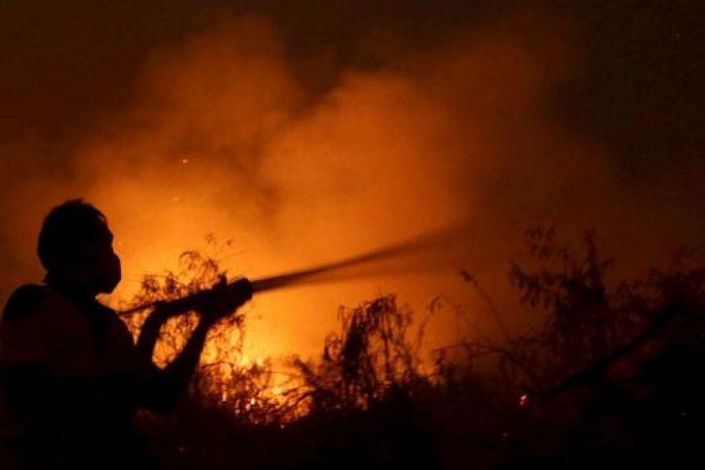 JEREBU AKIBAT KEBAKARAN HUTAN: Ahli bomba dilihat cuba memadamkan api yang merebak di kampung Simpang Pelabuhan berhampiran Palembang, pulau Sumatera, Indonesia, 7 September lalu. - Foto REUTERS