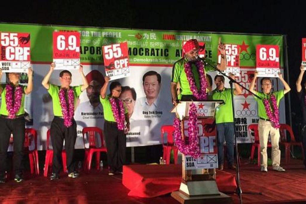 SERU SOKONGAN RAMAI: Calon-calon SDA bagi GRC Pasir Ris-Punggol memegang poster-poster menunjukkan slogan mereka yang menyentuh tentang isu Kertas Putih dan Kembalikan Wang CPF pada usia 55 tahun. – Foto HAIRIANTO DIMAN