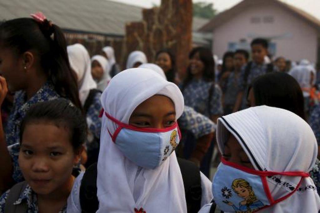 Pelajar memakai pelitup berjalan pulang ke rumah dari sekolah selepas mutu udara mencapai paras tidak sihat di Palembang pada Khamis (10 Sep). Gambar REUTERS