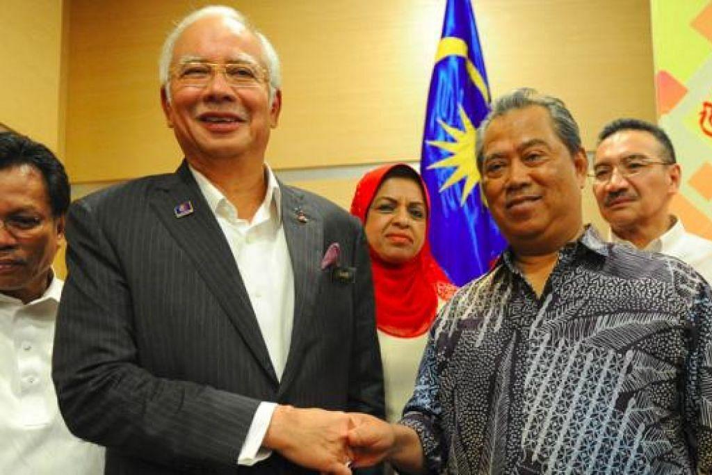 TETAP SETIA DENGAN UMNO: Datuk Seri Najib (dua dari kiri) bersalaman dengan Tan Sri Muhyiddin selepas mesyuarat Majlis Tertinggi Umno di ibu pejabat Umno kelmarin. Turut sama dalam mesyuarat itu adalah Datuk Seri Shafie (kiri). - Foto AFP