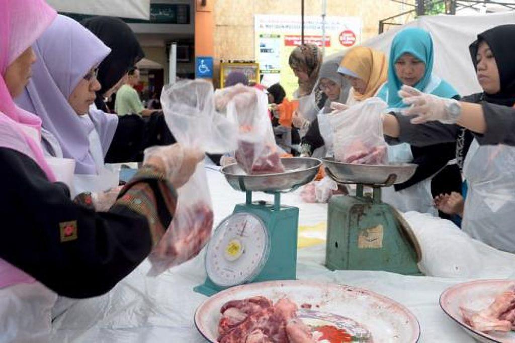 MENGORBANKAN TENAGA: Sekumpulan sukarelawan wanita membungkus daging korban di Masjid Al-Muttaqin pada Hari Raya Aidiladha tahun lalu untuk diagihkan kepada yang memerlukan. - Foto fail