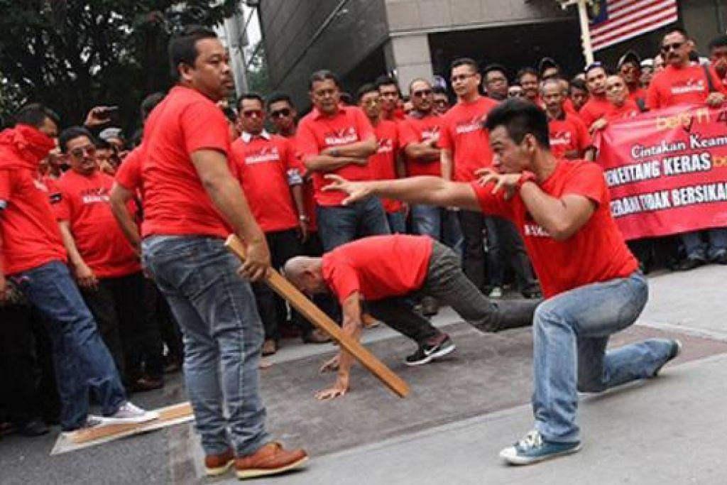 HANYA DEMONSTRASI SILAT?: Aksi ekstrem peserta kumpulan anti-Bersih 4.0 berbaju merah yang diadakan di depan kompleks beli-belah Sogo baru-baru ini mempamerkan demonstrasi lasak silat, dengan aksi menahan pukulan kayu serta memecahkan atap genting. - Foto THE STAR